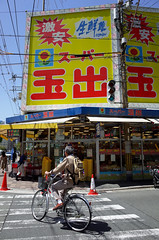 Symbol of Osaka... (Eric Flexyourhead) Tags: minamihorie 南堀江 nishiku 西区 osaka osakashi 大阪市 kansai 関西地方 japan 日本 city urban street streetscape cityscape streetscene streetphotography cyclist rider shop store market supermarket grocerystore supertamade colourful ricohgr