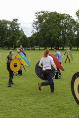 Historia Normannis Meadows June 2018-635 (Philip Gillespie) Tags: historia normannis central scotland sparring fighting shields swords axes spears park grass canon 5dsr men man women woman kids boys girls arms feet hands faces heads legs shins running outdoor tabards chain mail chainmail helmets hats glasses sun clouds sky teams solo dead act acting colour color blue green red yellow orange white black hair practice open tutorial defending attacking volunteer amateur kneeling fallen down jumping pretty athletic activity hit punch