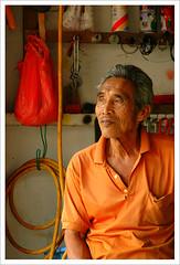 The Bike Master (elfonse) Tags: old portrait orange man shop dark grey eyes singapore d70s hard tools elderly stockphotos tanned nikonstunninggallery street5bob