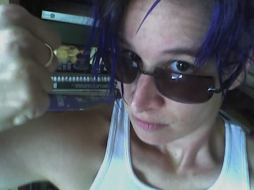 Person with blue hair and sunglasses holding a fist up to the camera.