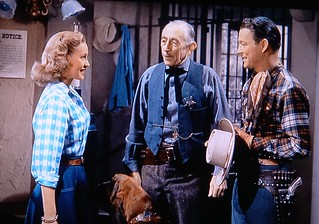 Sheriff Tad Osborne (Will Wright) introduces Roy Rogers to his niece Dixie (Penny Edwards) in