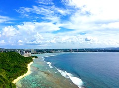 blue invasion (Yoman H) Tags: seascape landscape guam usa pacificocean ocean sea waves clouds sky blue green mountain hotels bay 關島 戀人岬 harmonvillage tamuning afternoon beach sand waters rocks vacation travel