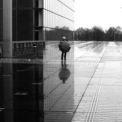 Behind the umbrella (pascalcolin1) Tags: paris13 bnf homme man pluie rain reflets reflection parapluie umbrella photoderue streetview urbanarte noiretblanc blackandwhite photopascalcolin 50mm canon50mm canon carré square
