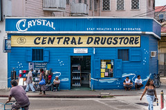 """License to sell Drugs & Poison"" (Phototravelography) Tags: belize belizecity blue colourful downtown drugs drugstore man people pharmacy pink poison shop streetlife streetphotograhy travel travelphotography woman wood ngc sign window door"