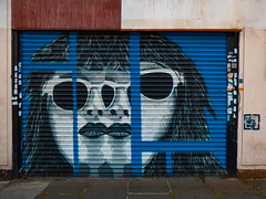 Double Vision (Steve Taylor (Photography)) Tags: wesone sunglasses sunnis lipstick two double doublevision hair art graffiti mural streetart sticker shop blue black grey white abstract lines shutter