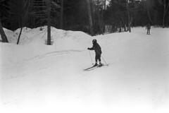 121169 21 (ndpa / s. lundeen, archivist) Tags: nick dewolf nickdewolf december photographbynickdewolf winter greenville maine mooseheadlake snow blackwhite bw 1969 1960s monochrome blackandwhite skitrip bigsquaw bigsquawmountain bigsquawmountainresort 35mm film skiing skier skiers people child trails slopes goggles boy