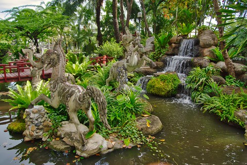 Sculptures and waterfall in the garden of Erawan museum in Samut Phrakan near Bangkok, Thailand