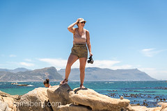 A young female photographer standing on top of a large rock seaside on Boulders Beach in Simon's Town, South Africa (Remsberg Photos) Tags: africa southafrica capetown coastal seaside woman youngwoman westerncapeprovince ocean photographer femalephotographer explore explorer adventure summertime summer caucasian adventurer simonstown boulderbeach westerncape