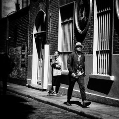 Swagger (Kieron Ellis) Tags: bars cobblestones man woman smoking hat sunglasses fedora street candid blackandwhite blackwhite monochrome