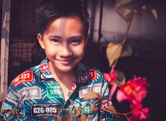 boy behind flowers (Hải Quyên) Tags: portraid portrait people vietnam vietnamese viet boy flowers flower face faces canon