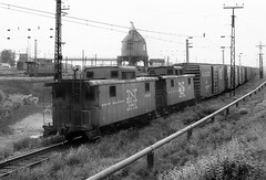 New Haven Railroad Caboose C-633, along with another, brings up the end of a manifest freight train that is in the Cedar Hill Yard at New Haven, Connecticut, July 1967 (alcomike43) Tags: newhavenrailroad newyorknewhavenhartfordrailroadcompany cedarhillyard newhavenconnecticut yard tracks rails rightofway ties roadbed ballast conventionaljointedsectionrail electrification catenary caboose railroads trains freighttrains freightcars boxcars coalingtower catenarysupportstructure ac c633 photo photograph bw blackandwhite old historic vintage classic