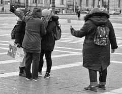 Follow The Phone (tcees) Tags: heroessquare hosöktere budapest hungary woman men people rucksack mobilephone coat hood car pedestrians road traffic trafficlights bollards square lampposts gate selfiestick pest urban nikon d5200 1855mm bw mono monochrome blackandwhite streetphotography street