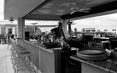 Bartender-in-waiting (tishpitt1) Tags: bartender streetphotography alone bored waiting bar saloon roof rooftop wyvernhotel puntagorda florida monochrome blackandwhite panasoniclx7