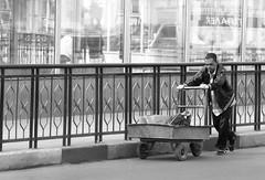 Dushanbe Cart Man (peterkelly) Tags: digital canon 6d bw asia tajikistan dushanbe gadventures centralasiaadventurealmatytotashkent street railing man pushing cart hat glass window