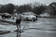 Don't care if it's raining, but I'll skate shirtless anyway (Stefen Acepcion) Tags: street bw black white urban road canada oakville ontario rain wet transportation streetphoto spring may skateboard splash mark gloom clouds