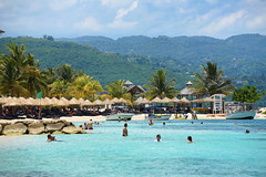 Splash Wid Mi,Mon! (Poocher7) Tags: beach sand people swimming wading water ocean sea thatchedumbrellas shelter palmtrees boats glassbottomboat mountains clouds sunny loungechairs mobay montegobay resort jamaica westindies caribbean