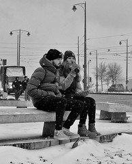 Why Are We Sitting In The Snow? (tcees) Tags: szentgellérttér budapest hungary woman men people forrásház trafficlights lampposts bottle snow snowing bench car van road pedestrians traffic buda nikon d5200 1855mm urban bw mono monochrome blackandwhite coat seat streetphotography street cold freeze freezing hat boots