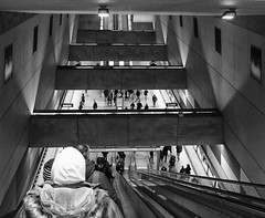 Down Into The Depths (tcees) Tags: móriczzsigmondkörtér undergroundstation m4 people men women escalator train clock sign budapest hungary urban x100 fujifilm finepix bw mono monochrome blackandwhite wall lights shadow grills platform streetphotography street metro