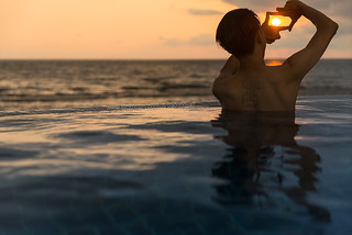 A young man enjoy sunset and sea in the pool by the sea.