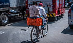 2018 - Mexico City - Bikers (Ted's photos - Returns 23 Jun) Tags: 2018 cdmx cityofmexico cropped mexico mexicocity nikon nikond750 nikonfx tedmcgrath tedsphotos tedsphotosmexico vignetting bike bicycle streetscene street riders people peopleandpaths ballcap couple two duo wheels shadow shadows orange