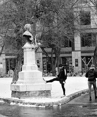 Give Us A Leg Up (tcees) Tags: széchenyiistvántér budapest hungary snow snowing people men women streetphotography street urban bw mono monochrome blackandwhite nikon d5200 1855mm pest pavement statue bust jogger tree building bike bicycle cycle rucksack hat sidewalk winter cold freeze freezing windows door