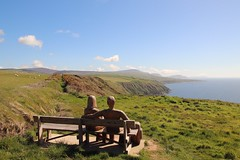 Seat with a Sea View (RoystonVasey) Tags: roaming email upload canon eos 77d sigma 1770mm zoom sea view bench wooden carving people
