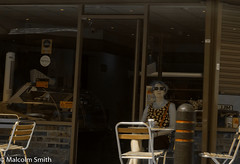 Cafe Life 22 (M C Smith) Tags: gold woman sitting tables chairs windows reflections pentax k3 letters bollard sign bricks counter door open lights shutters