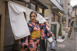 British woman in kimono at the entrance of traditional Japanese restaurant