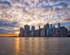 Wild Manhattan Sunset (RobertCross1 (off and on)) Tags: 1250mmf3563mzuiko brooklyn brooklynbridgepark em5 eastriver longexposure manhattan nyc newyork omd olympus architecture atardecer buildings city cityscape clouds landscape puestadelsol reflection skyline skyscrapers sunset urban water