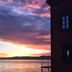 Fiery fjord (halifaxlight) Tags: norway hordaland bergen bergenfjord fjord sunset clouds sea reflections mountains dock building windows square