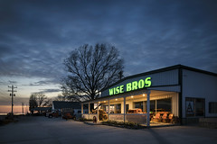 Wise Bros (Notley Hawkins) Tags: notley notleyhawkins 10thavenue httpwwwnotleyhawkinscom missouriphotography notleyhawkinsphotography ruralphotography architecture spring farmequipment wisebros callawaycounty callawaycountymissouri rural facade shop wisebrothers light windows tractor april missouri 2018 sky clouds sunset bluehour window tree sign road i70 interstate70