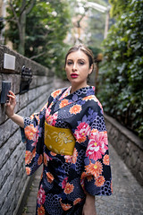 British woman in kimono standing on narrow street (Apricot Cafe) Tags: img78095 asia caucasianethnicity healthylifestyle japan japaneseculture kagurazaka kimono newyear tamronsp35mmf18divcusdmodelf012 tokyojapan backlit beautifulwoman brownhair buildingexterior candid capitalcities carefree charming colorimage cultures day formalwear grace hairstyle happiness leaning lifestyles longhair lookingatcamera narrow nature oneperson outdoors people photography smiling sunlight threequarterlength tourism tradition traditionalclothing traveldestinations tree visiting walkway wall women youngadult
