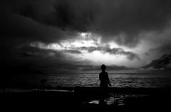 Un héros très discret... (Sabine-Barras) Tags: suisse switzerland ciel sky clouds nuages argentique argentic monochrome blackandwhite bnw bw dark lac lake water eau paysage landscape statue sculpture