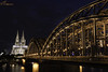 Kölner Dom (Gavmonster) Tags: gswphotogrpahy nikon d7500 koln cologne germany cathedral kölnerdom bridge railbridge gothic rhine northrhinewestphalia night longexposure 20seconds steel arch lights river clouds railway boat architecture girders spires towers worldheritagesite leadingline