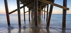 under the pier (lucmena) Tags: architecture beach california longexposure malibu manmade ocean outdoor perspective pier scenic sunset waves losangeles ca usa ngc