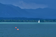 Bad weather takes off from the mountains ... (W_von_S) Tags: chiemsee bavaria bayern berge mountains alpen alps wasser water lake lakechiemsee clouds wolken himmel sky dark dunkel blue blau streifen stripe türkis turquois red rot boje buoy landschaft landscape panorama paysage paesaggio boat boot segelboot sailboat sony sonyilce7rm2 wvons werner flickrtreffen outdoor badweather unwetter see minimalistisch minimalism