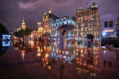 Bund Reflection (Stuck in Customs) Tags: china shanghai treyratcliff stuckincustoms stuckincustomscom hdr hdrtutorial hdrphotography hdrphoto aurorahdr reflection woman umbrella wet rain water classic architecture cityscape night lights bund