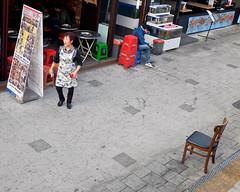 Restaurant Woman and Sidewalk Chair (Mondmann) Tags: hongdae seoul korea southkorea rok republicofkorea asia eastasia woman restaurant sidewalk chair candid street streetphotography mondmann fujifilmx100s korean koreanwoman