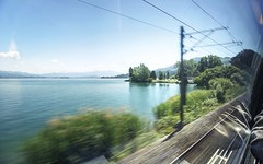 Riding the train along Lake Zurich (PeterThoeny) Tags: lakezurich richterswil switzerland zurich lake railway train track railwaytrack transportation motion blur motionblur day clear sony a6000 selp1650 1xp raw photomatix hdr qualityhdr qualityhdrphotography water grass tree sky fav100
