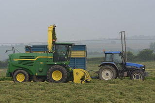 John Deere 7480 SPFH filling a Kane Trailer drawn by a New Holland TM150 Tractor