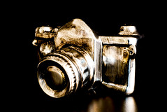 A modern version of a camera in silver and gold (jacqueline440) Tags: art buttons camera capture creation design device electronics equipment filament flash focus frame gold graphic image isolated lens media modern photgraphic photo photographing photographs photography picture shiny shoot shutter sign silver simple snapshot symbol technology