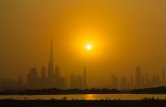 Into the Dubai sunset. (Gergely_Kiss) Tags: buildingsilhouette desert sunsethaze haze burjkhalifa sunset dubaisunset uae dubai