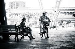 Eldery man and woman talking in the park - Yuanshan park, Taipei, Taiwan (BryonLippincott) Tags: 50mm14 bw blackandwhite resting shadows sony sonyalpha thailand travel travelbangkok backlit bicyclebench conversation dresssandals explore exploring friends friendship hatbasket interesting man mostinteresting oldman oldwoman park roof shade shadow shoes sitting talking tires woman taipei taiwan taiwanese asia asian city urban bench benches elderly old bicycle riding candid documentary acquaintances outside bright