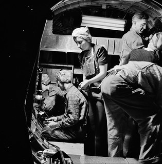 A team of workers completing assembly and fitting operations on the interior of a fuselage section of a B-17F, 1942.