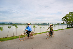 Riding bicycles along the river (BryonLippincott) Tags: vietnam vietnamese vietnameseculture asia southeastasia countryside country hanoi rural agriculture farm farming ruralscene farmscene farmland mountains fog haze houses industry production community fields landscape rurallandscape bicycle biking riding pedaling trees bluesky clouds