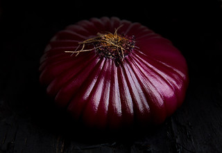 Red onion on black rustic background. Close up. Macro