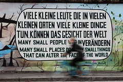 To change the world (Elios.k) Tags: horizontal outdoors people oneperson man cycling cyclist bicycle bike movement motion motionblur slowshutterspeed transportation eastsidegallery graffiti wall mural africanproverb manysmallpeople text art streetart kanialavi artist german murielraoux openairgallery mühlenstrase friedrichshainkreuzberg colour color berlinwall berlinermauer travel travelling october2017 canon 5dmkii photography berlin germany deutschland europe