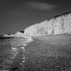 Brothers & Sisters (Lloyd Austin) Tags: brothers sisters walking sevensisters birlinggap beach eastsussex chalkcliffs sand pebbles rocks sea shoreline coastline coastal nationaltrust water tidal view vista people sky cloud exposure texture contrast black white grey bw bnw blackandwhite blackwhite mono monochrome scale scenic story landscape uk waves sigma1750mm d7200 dramatic nikon nature