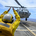 Sailor directs a helicopter from the flight deck of USS Antietam (CG 54).
