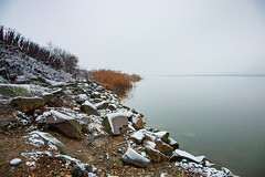 Lakeside in winter (Raoul Pop) Tags: stone reeds snowfall solitude rocks lake shore winter cold somewhere transilvania romania ro